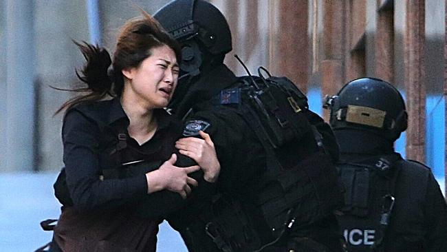 A hostage runs to armed tactical response police officers for safety after she escaped.