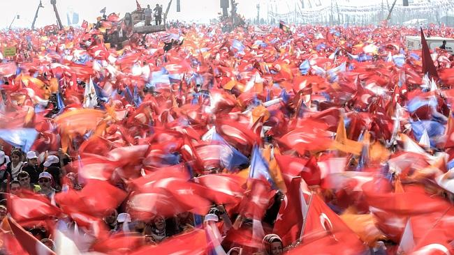 Rally ... Supporters of Turkey's Prime Minister cheer and wave Turkish and AK Party flags during an election rally in Istanbul on Sunday. Picture: AFP