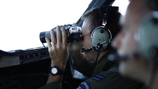 New search zone... A pilot on the flight deck of a Royal New Zealand air force P-3K2 Orion aircraft searching for the missing plane. Picture: Jason Reed/AP