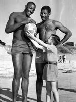 Harlem Globetrotters Tim Spencer and Ernest Wagner sign a beach ball for John Nairn, 9, at Henley Beach in 1956 during the team's Adelaide visit.