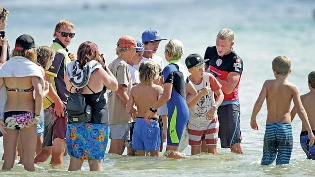 Mick Fanning is surrounded by fans after moving through round 3 of the Quiksilver Pro.