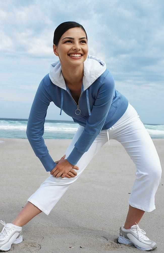 Close-up of a woman exercising on the beach. Stretch. Stretching. Generic image.