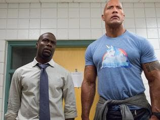 "This image released by Warner Bros. Entertainment shows Kevin Hart, left, and Dwayne Johnson in a scene from, ""Central Intelligence."" The movie had a relatively muscular weekend, with a better-than-expected $34.5 million, according to comScore estimates Sunday, June 19, 2016. (Claire Folger/Warner Bros. Entertainment Inc. via AP)"