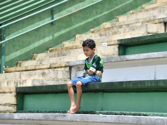 A boy sits alone on the stands during a tribute to the players of Brazilian team Chapecoense Real.