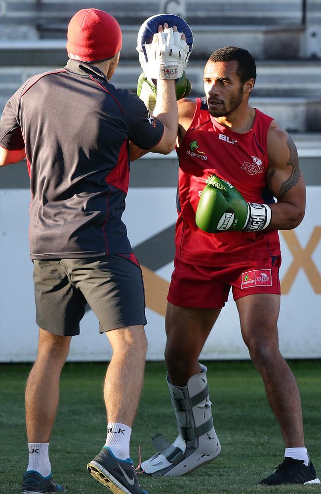 Wearing a moon boot on his right foot, Will Genia engages in some boxing training at Ballymore.