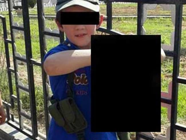 Shocking picture ... a boy security agencies believe to be Australian Khaled Sharrouf's son holds the decapitated head of a soldier in the Syrian city of Raqqa. It was posted on Twitter. Source: Supplied