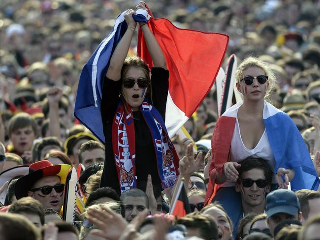 French fans hold the French national flag as they watch on a giant screen the FIFA World Cup 2014 quarter-final football match between Germany and France, Germany on July 4, 2014 in Berlin.