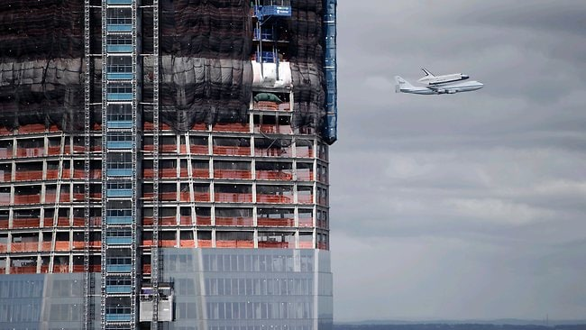 These are the last voyages... Space shuttle Enterprise flies past the World Trade Center construction site. Picture: AP