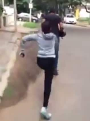 The woman chases the man down the street.