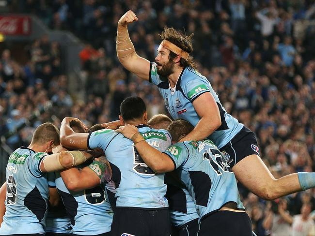 Aaron Woods jumps onto his Blues teammates to celebrate a try by Trent Hodkinson.