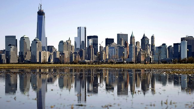 New York's Lower Manhattan skyline, including the One World Trade Center, left, is reflected on the water.