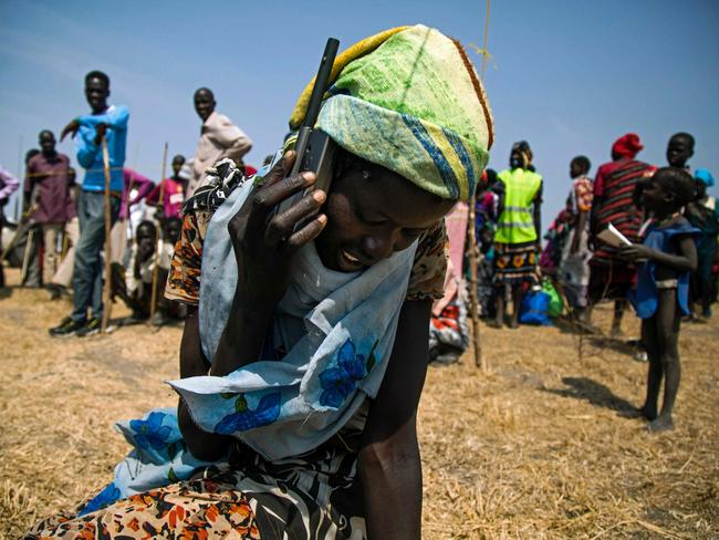 A woman from Thonyor, South Sudan, uses a satellite phone provided by the International Committee of the Red Cross to call her lost relatives.
