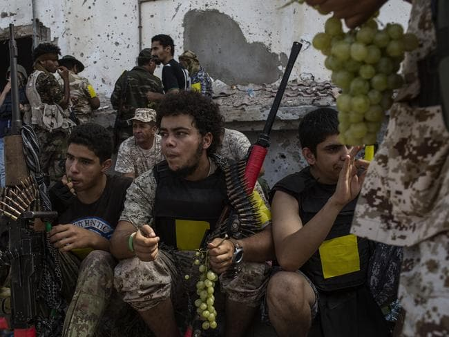 Fighters loyal to Libya's Government of National Accord eat grapes during a break on the western frontline against Islamic State. Picture: Fabio Bucciarelli