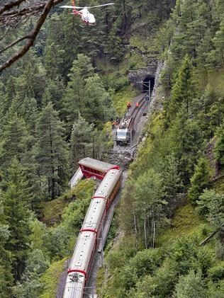 A helicopter flies over the train after it was derailed by a landslide. Picture: Michael Buholzer