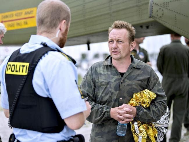Peter Madsen talks to a police officer after his submarine sank in the sea outside Copenhagen Harbour. Picture: AFP