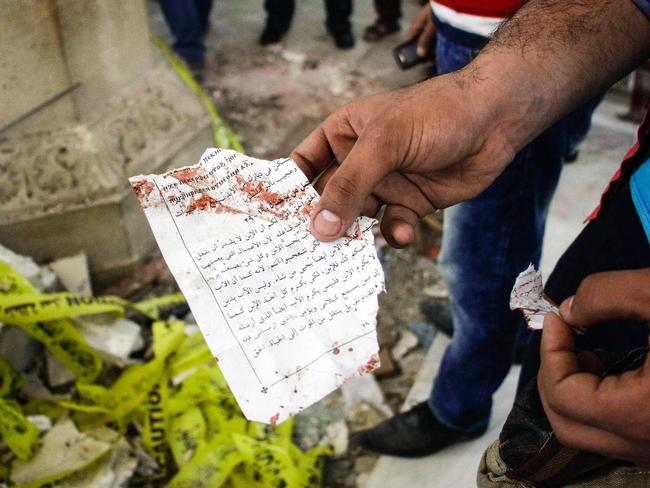 An Egyptian holds out torn a page from a prayer book inside the Mar Girgis Coptic Orthodox Church in Tanta. Picture: AFP