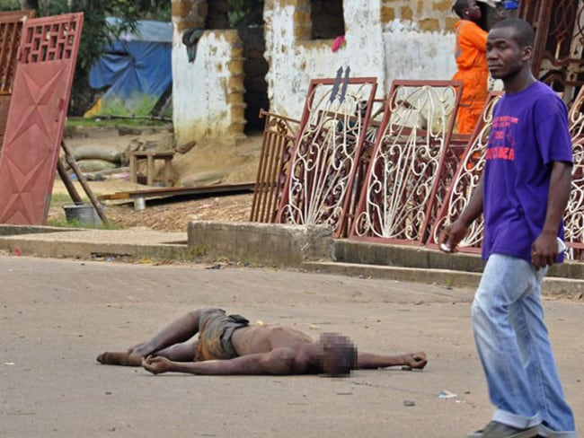 A man walks past the body of an Ebola victim in Liberia as the country struggles to contain the deadly virus.