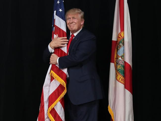 Donald Trump hugs the American flag as he arrives for a campaign rally in Tampa, Florida. Picture: Joe Raedle/Getty Images/AFP