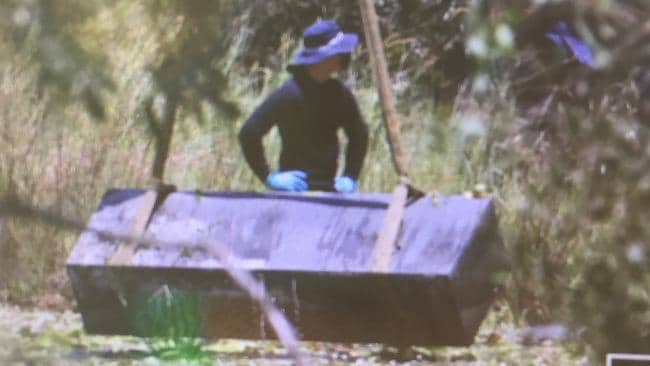 Police retrieve a large metal box from a dam following a murder investigation. Picture: Jono Searle