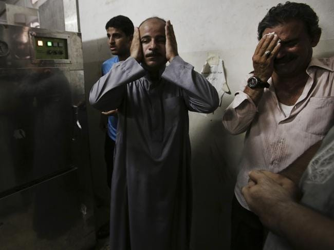 Palestinian relatives mourn in the morgue of Shifa hospital following an explosion that killed 10 people. Picture: Adel Hana