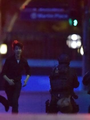 A terror-stricken Jarrod Hoffman runs to police as the siege nears its end. Picture: Peter Parks