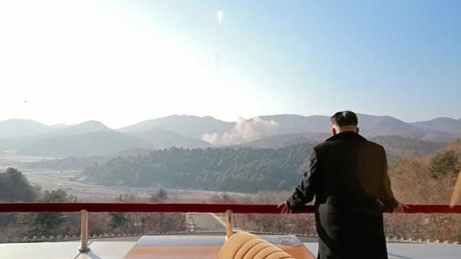 Clouds of smoke lie in the background as Kim Jong Un watches the rocket launch. Picture: AFP/ North Korean TV