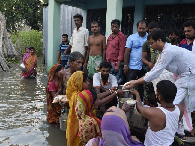 Indian villagers receive relief food near the submerged houses by flood waters in Gazole village at Malda district in the Indian state of West Bengal on August 22, 2017. Picture: AFP.