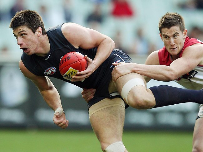 Melbourne v Carlton. MCG. Matthew Kreuzer looks for an option as he is tackled by Jeremy Howe