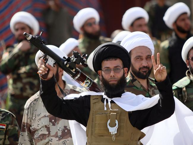 Crisis..An Iraqi Shiite fighter poses flashing the sign of victory during a parade on June 21 in Baghdad. Picture: AFP