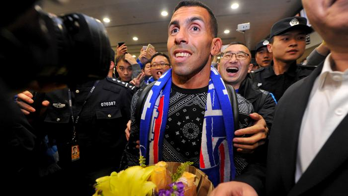 Argentine striker Carlos Tevez makes his way through the arrivals halls at Shanghai Pudong International Airport in Shanghai on January 19, 2017. Tevez arrived to a rousing welcome from hundreds of fans in Shanghai, where he will join local side Shenhua in a deal that reportedly makes him the world's top-earning footballer. / AFP PHOTO / STR / China OUT