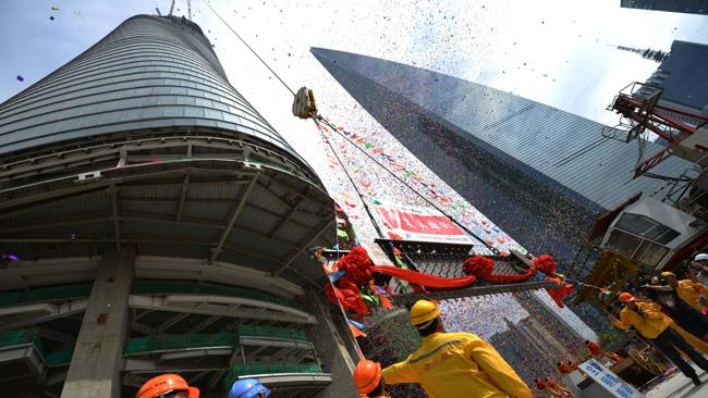 Construction workers watch as the final steel beam is hoisted up. Picture: AFP