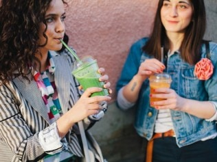 Two female friends drinking smoothies outdoors