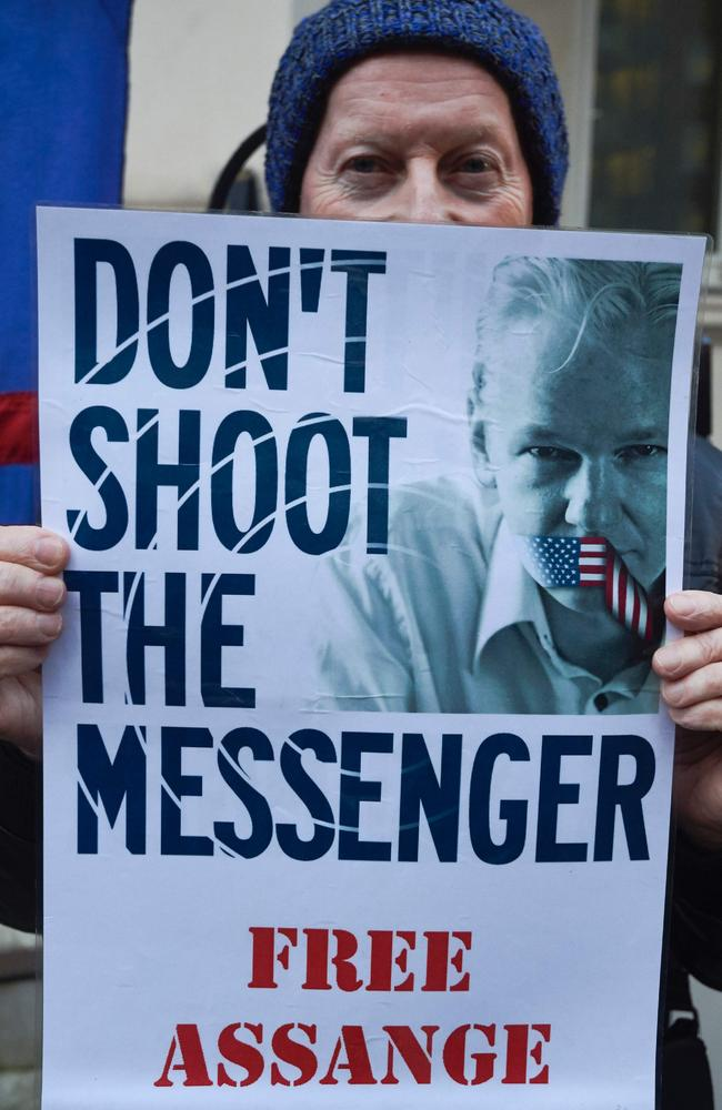 A supporter of WikiLeaks founder Julian Assange holds a poster outside the Ecuadorean embassy.