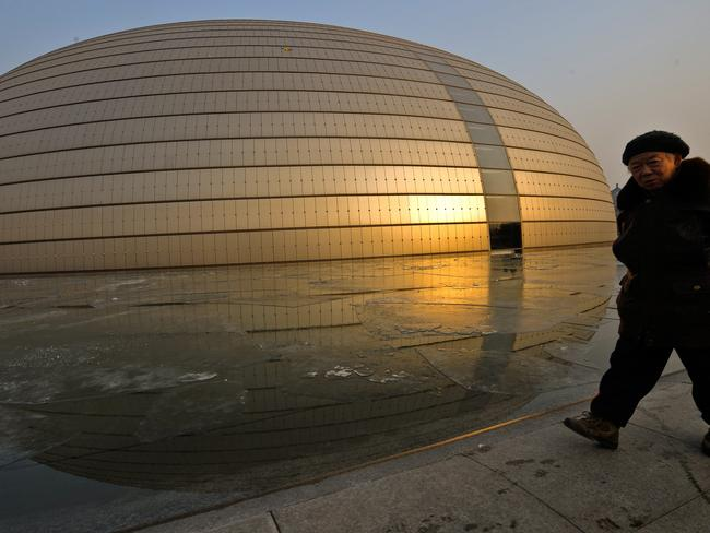 An elderly woman walks past the China National Grand Theatre in Beijing, another building which is considered to be not very aesthetically pleasing.