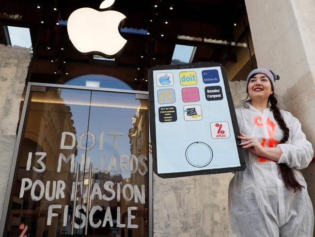 "An activist from the Association for the Taxation of financial Transactions and Citizen's Action posing next to an inscription which translates as ""(Apple) owes 13 billion (euros) due to tax evasion"" in front of an Apple store in Paris during a demonstration. Picture: Thomas Samson"