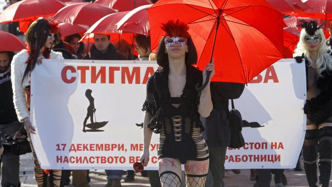 People carrying red umbrellas march through downtown Skopje, Macedonia, marking the International Day to End Violence against Sex Workers last month. Image: AP Photo/Boris Grdanoski.