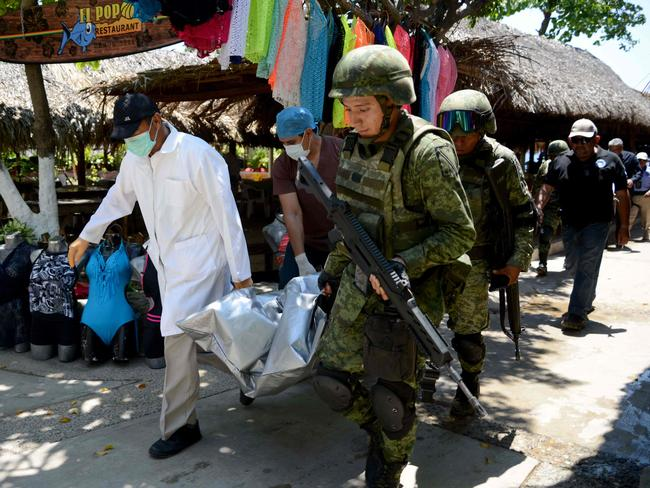 Forensic personnel and Mexican soldiers carry the corpse of the murdered man, who was found in Caletilla Beach, Acapulco on April 15. Picture: Francisco Robles/AFP