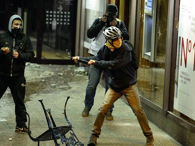 A masked demonstrator ... breaks the windows of a bank during clashes at the end of the m