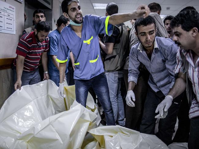 So many dead ... Palestinian medics from Gaza City's al-Shifa hospital react while body bags with the remains of children arrive after an Israeli air strike in Gaza City killed 11 people, including five children.