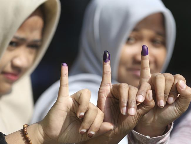 Muslim women shows their ink-stained fingers after voting during the runoff election in Jakarta, Indonesia, Wednesday, April 19, 2017. Picture: Achmad Ibrahim