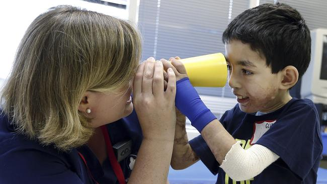 Learning his motor skills ... therapist Katherine Hartigan interacts with Ihor Lakatosh at Shriners Hospital for Children in Boston. Picture: Michael Dwyer