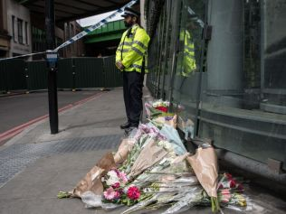 A police officer stands near flowers after terror attack, June 8 2017. Photo: Carl Court/Getty Images.
