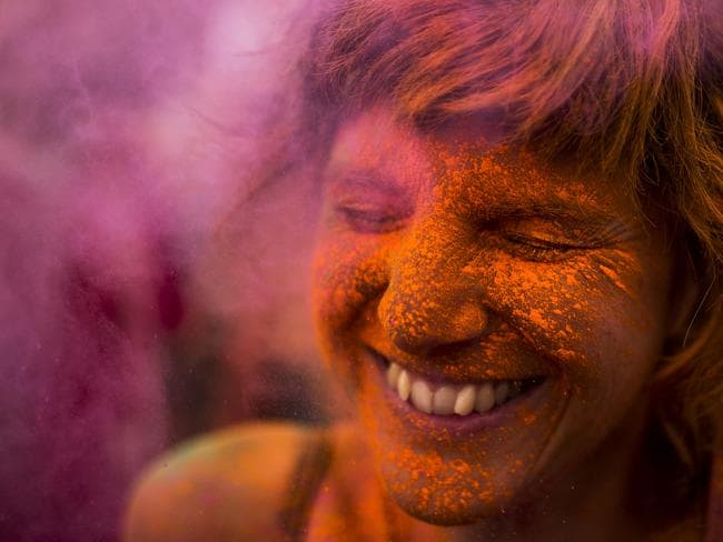 A reveller is covered in coloured powder, during the Holi Festival. Picture: AP