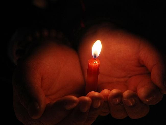 Clinging to hope...A high school student holds a candle during a vigil for passengers of the missing Malaysia Airline flight MH370 in Lianyungang, China's as relatives demand answers. Picture: AFP