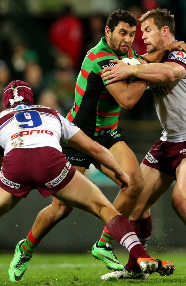 South Sydney's Alex Johnston attempts to bust the tackle of Manly's Brenton Lawrence.