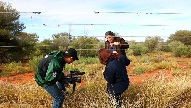 Toohey helps Lorelle Trickett through a fence to get to a location to search at Barrow Creek.