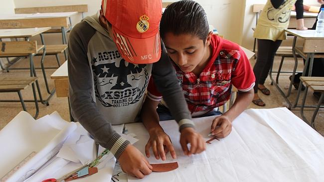 Yaarob helping Ahmad (R) with one of his scenes during an animation workshop run by Save the Children in Lebanon, facilitated by photographer and filmmaker Diaa Maleab.
