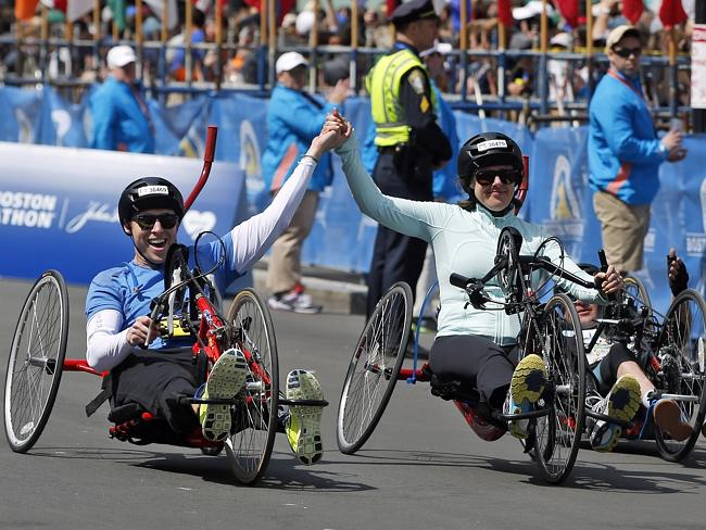 Boston Marathon husband and wife bombing survivors Patrick Downes and Jessica Kensky, who each lost a leg in last year's bombings, roll across the finish line in the 118th Boston Marathon. Picture: Elise Amendola