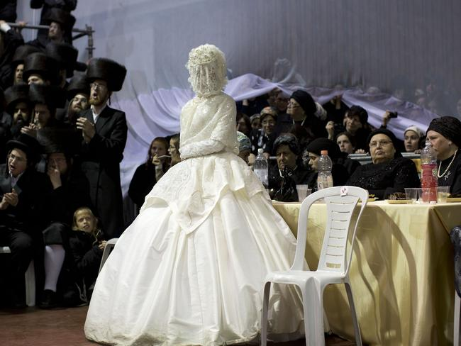 A thin curtain behind the bride divides the men and women sections. Picture: AP Photo/Oded Balilty