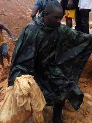 A man is seen carrying the remains of a loved on to the morgue in Freetown. Picture: AFP
